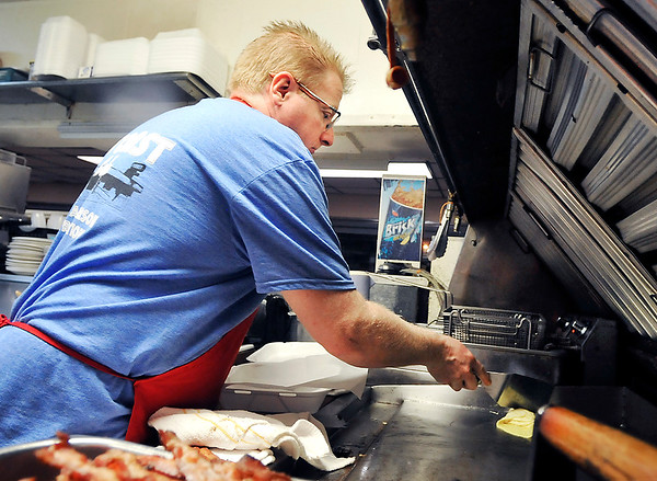 John P. Cleary | The Herald Bulletin<br /> Toast Restaurant co-owner Chris Gentry works the grill as he prepares a to-go order.