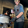 John P. Cleary | The Herald Bulletin<br /> Joshua Beers applies bead sealer to this rim as he mounts tires on this morning.