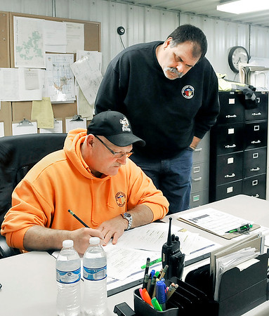 John P. Cleary | The Herald Bulletin<br /> Madison County Highway Department general foreman Gerald Imel fills out the crew worksheets for the day as brush crew foreman Aaron Hopkins checks the list a little after 7 a.m. on this rainy Wednesday.