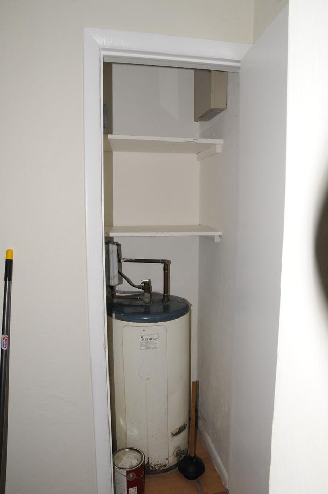 storage above water heater in hallway.