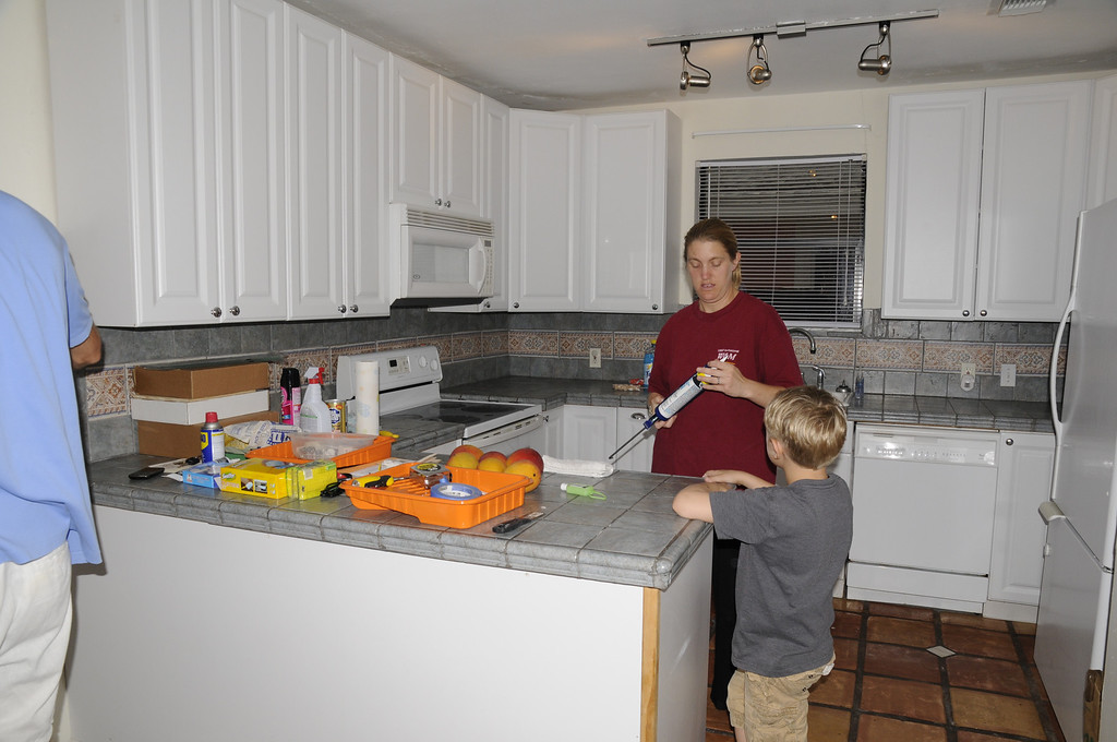 kitchen has large fridge and bottom freezer on right. You can see the dishwasher.  The sink is to the left of the dishwasher. You see you stove and plenty of cabinet and tile counter top.