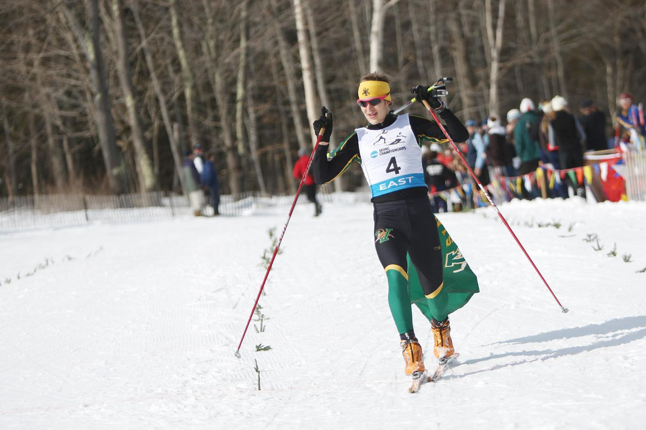 The University of Vermont's Franz Bernstein takes the win in style with a Catamount flag draped over his shoulder at the Men's 20k Skate event during the Middlebury Carnival and Eastern Championship races at the Rikert Touring Center in Ripton, VT.<br /> <br /> Credit: Lincoln Benedict / EISA