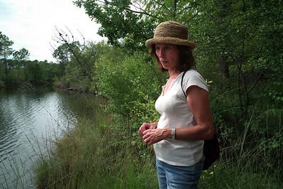 Véronique avec son chapeau devant un étang.