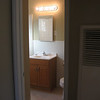 Bathroom with new tile floor, new vanity cabinet, top, and Moen faucet, medicine cabinet and light fixture.
