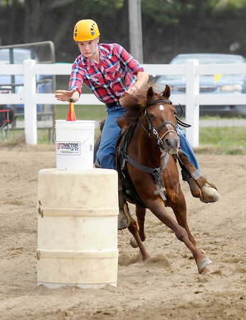 "Don Knight/The Herald Bulletin<br /> Camden Nunley reaches for the flag during the Senior Flags 56"" and Under class during the Horse and Pony show at the 4-H Fair on Friday. Camden and his horse Star finished second."