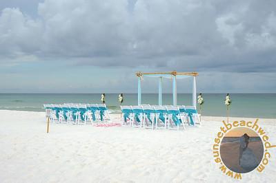 Turquoise & White Fabric, Turquoise Chair Sashes, Shown with Tiki Torches next to Arbor