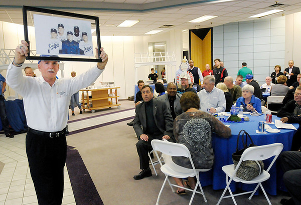 Keith Trent holds up a photo as it is auctioned.