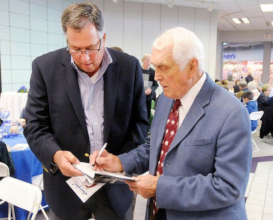 "Carl Erskine autographs a book for Dan Dykes during a reception at the Mounds Mall before the premiere of the movie ""42"" on Thursday."