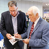 """Carl Erskine autographs a book for Dan Dykes during a reception at the Mounds Mall before the premiere of the movie """"42"""" on Thursday."""