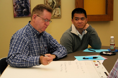 Br. Long Nguyen looks on as Fr. Paul Kelly records table discussions.