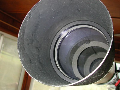 A close-up of the Jaegers 6 inch lens, cell and dew cap. The bluish or purplish color of the lens is a coating of Magnesium Floride to increase light transparency.  The lens is a little dusty in this shot in November 2004. I cleaned up the elements since then!!