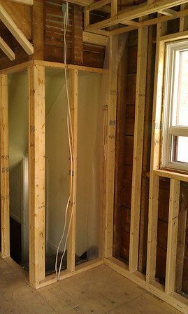 Kitchen: framing a bulkhead to hold services, removed superfluous ceiling dropdown. Looking through wall to basement stairs.
