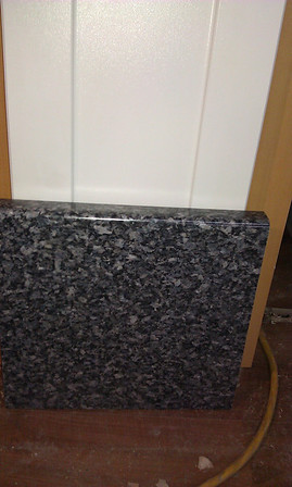 "White Shaker cabinets and ""granite look"" laminate countertop. Ordered ""bullnose"" front edge for $200 extra. The countertop was ""discontinued"" and we found out after buying the floor & splash tiles to match it."