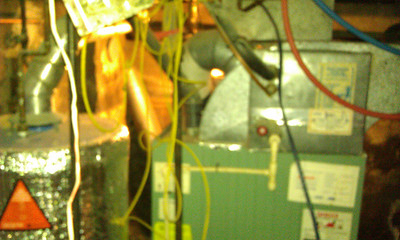 Basement: close-up of water heater and furnace. Light in furnace alcove is on. Red and blue are water pipes.