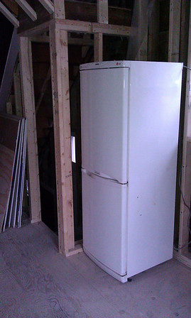 Kitchen: final location of fridge. It *just* fits between wall and left edge of window. Door of fridge will have to be rehung to swing out left.
