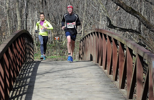 Runners Jenna Sheppard of Madison Lake and Ross Kohn of North Mankato cross a bridge over Seven Mile Creek during Saturday's 7@7 Trail Race. Photo by Pat Christman