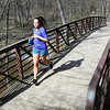 A runner crosses a bridge over Seven Mile Creek during Saturday's 7@7 Trail Race. Photo by Pat Christman