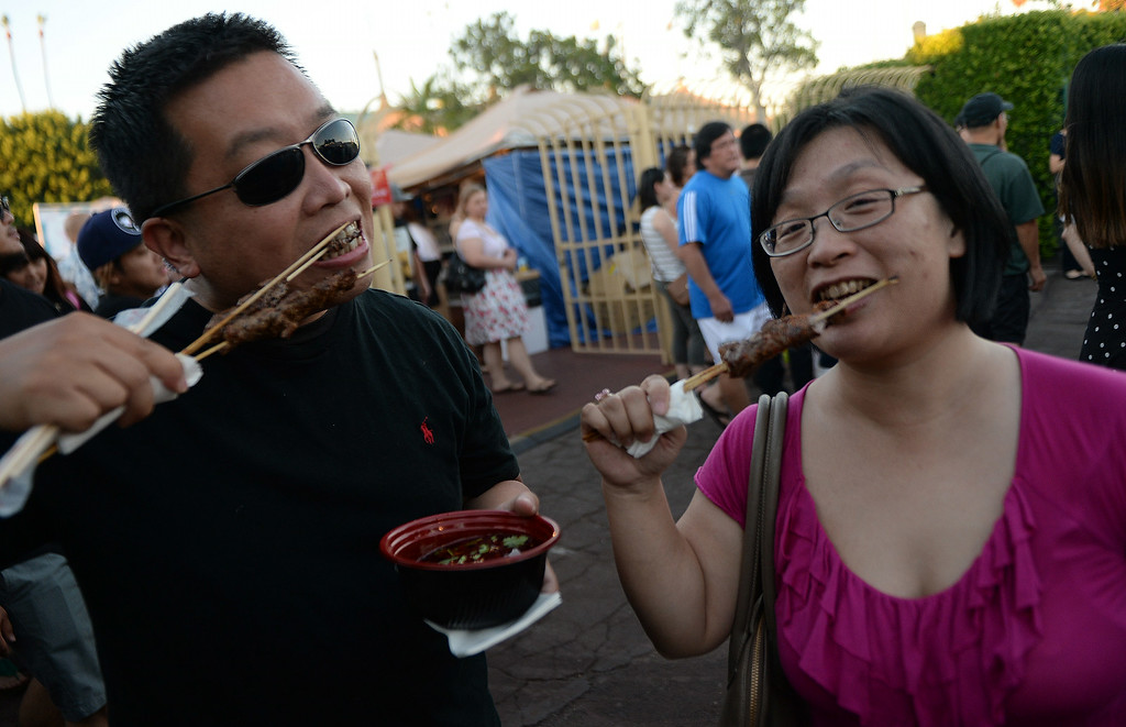 . Juliet Yao, right, along with Justin Lu of Sherman Oak enjoy dinner from the Bejing Tasty House during the 626 Night Market at Santa Anita Park in Arcadia, Calif., on Saturday, Aug. 16, 2014.  (Photo by Keith Birmingham/ Pasadena Star-News)