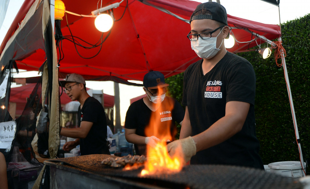 . Cooks from the Bejing Tasty House cook meat as thousands eat, shop and listen to music during the 626 Night Market at Santa Anita Park in Arcadia, Calif., on Saturday, Aug. 16, 2014.  (Photo by Keith Birmingham/ Pasadena Star-News)