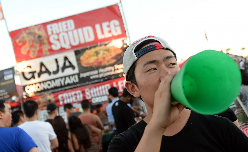 . Daisuke Urakawa from Gaja out of Torrance tries to get locals to try the fried squid leg during the 626 Night Market at Santa Anita Park in Arcadia, Calif., on Saturday, Aug. 16, 2014.  (Photo by Keith Birmingham/ Pasadena Star-News)