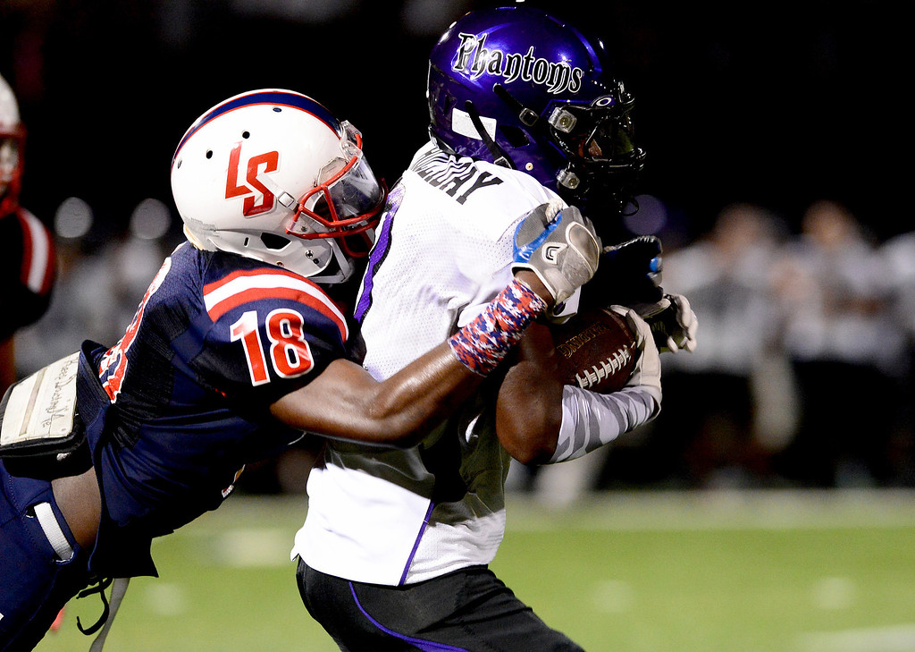 . La Salle\'s Brandon Mulligan (18) takes down Cathedral\'s Martaveous Holliday (3) during the first half of Friday night\'s game at La Salle High School in Pasadena, on August 30, 2013. (Photo by Sarah Reingewirtz/Pasadena Star-News)