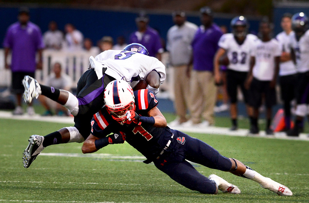 . La Salle\'s Jared Akins (1) takes down Cathedral\'s Martaveous Holliday (3) during the first half of Friday night\'s game at La Salle High School in Pasadena, on August 30, 2013. (Photo by Sarah Reingewirtz/Pasadena Star-News)