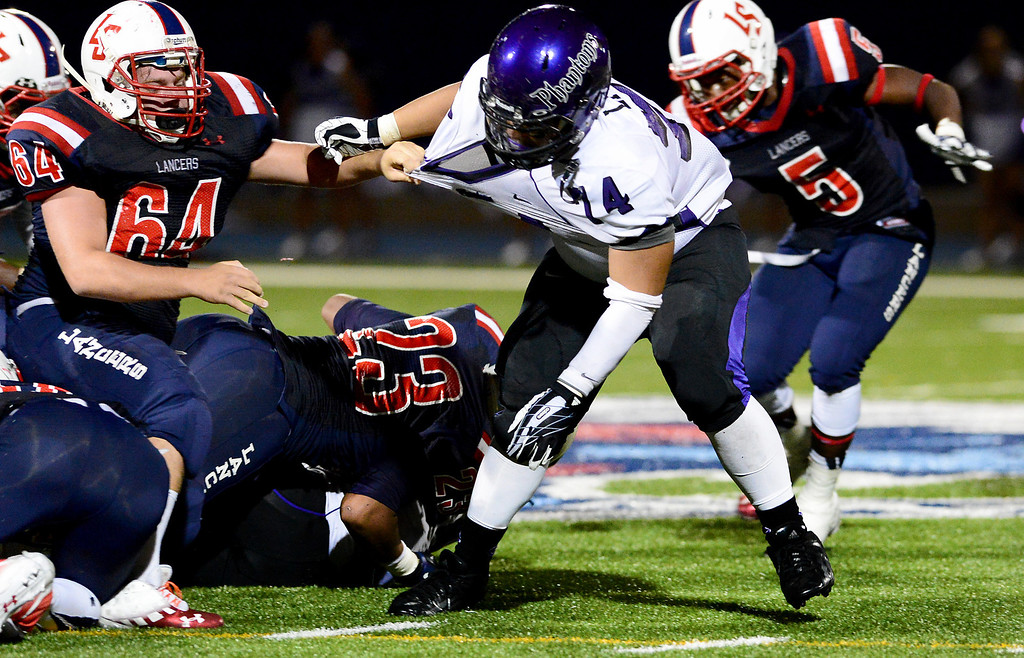 . La Salle\'s Jason Young (64) takes down Cathedral\'s Jahmaree De Sett (24) during the first half of Friday night\'s game at La Salle High School in Pasadena, on August 30, 2013. (Photo by Sarah Reingewirtz/Pasadena Star-News)