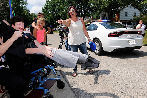 Don Knight | The Herald Bulletin<br /> Matthew Robinette, left, reacts as a parade for his 21st birthday travels past his home on Saturday. Mathew loves loud noises and sirens and his mother Kim Davis-Robinette asked friends to come by and honk their horns. Her request went viral on Facebook and hundreds turned out and the parade lasted for 90 minutes.