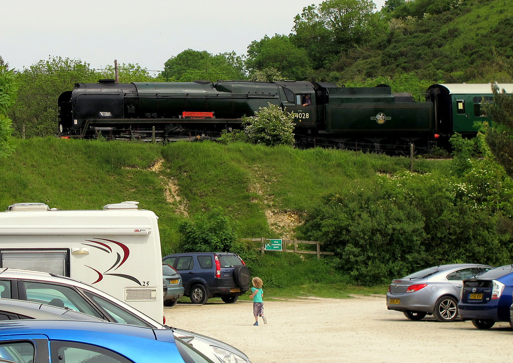 A young boy runs to wave to a passing train from Swanage.