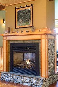The Dining and Living Room share a two sided fireplace accented with rocks from Giscome - known as 'Giscome Green'.