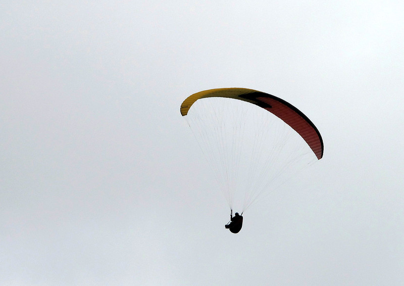 A paraglider drifts silently past directly over the cliff edge.
