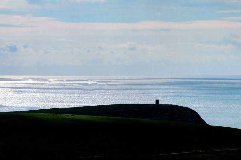 """Bright sunshine over the sea brings the Clavell Tower, Kimmeridge ( <a href=""""http://en.wikipedia.org/wiki/Clavell_Tower"""">http://en.wikipedia.org/wiki/Clavell_Tower</a> ) into sharp profile<br /> while a shaft of sunlight dimly illuminates some sheep grazing to the left."""