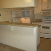 Kitchen with new refrigerator, with electric stove and micro wave.