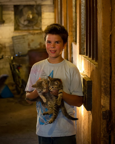 Tomy stands in the barn holding two kittens
