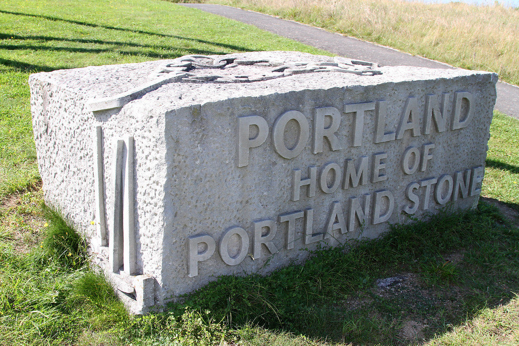 A carved Portland Stone block on the entrance road.   The items depicted on the side and top are mason's tools and lifting chain.