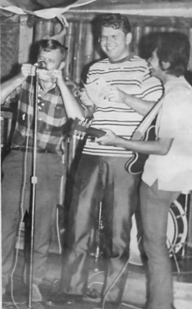 """This is Richard Cope and I in the P.I. celebrating our survival of a near death experience. I play the peso and comb, backed up by Airman Cope on vocals. Rollie plays lead guitar in a Caviti City night spot. We have good reason to be happy, having just survived falling from the sky over Cam Rahn Bay. Life is new that night and there is  pure joy and goodness in simply being. Earlier that day, you see, we had been pinned to the overhead of a falling Lockheed Super Constellation. There's part of me still, living where the wind still wails like a siren as we dive. Cope still hangs onto a milk can and I still hold  my guitar frozen in mid song. We had been stowaways on the Navy troop transport which is why we weren't strapped into a seat like the rest of the dying men. Cope and I aren't even on the roster,but we are very much among our brothers in that moment. We got into this situation by spending the evening buying beers for crusty old Chief Traxler. The chief is the father of fellow Cam Rahn photographer Buck Traxler, and he also happened to be the Plane Captain of the falling Super Constellation.  Sometime around three in the morning, Chief Traxler agreed to sneak us onto the craft. Overloaded already, two more souls on board won't hurt we all allow at that cloudy morning hour. Chief Traxler says we should stay hidden in the crew's bunk area until the bird achieves lift off. """"About the time we're airborne boys,"""" Chief Traxler says, """"ain't nobody gonna care if you've stowed away or not."""" Now with G-forces on our cheeks, the realization of imminent death is terrifying. I'm overwhelmed by the unfairness of looming Death. I had been singing at the front of the plane when the fall started. Cope and I think emerging from hiding with a bawdy song would be funny. It was then, in that moment, I see the first miracle.  Light comes through the window and illuminates the face of one of the sailors. He looks like an angel. All the passengers are facing me, but light comes from t"""