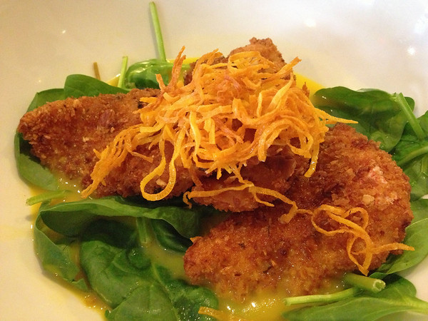 Snapper filets crusted with almonds on a bed of spinach in broth and topped with sweet potato shavings