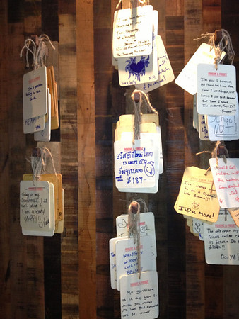 Messages handwritten on thin pieces of wood and hung with string on a restaurant wall