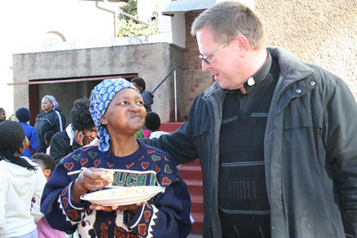Fr. Peter catches up with a member of the St. Teresa community.  He had previously served at the mission.