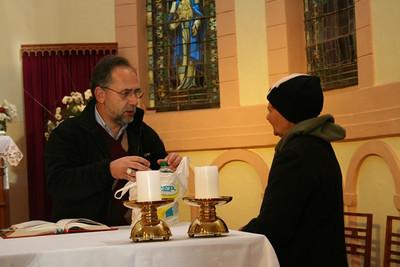 Bishop Adam blesses water for a parishioner.