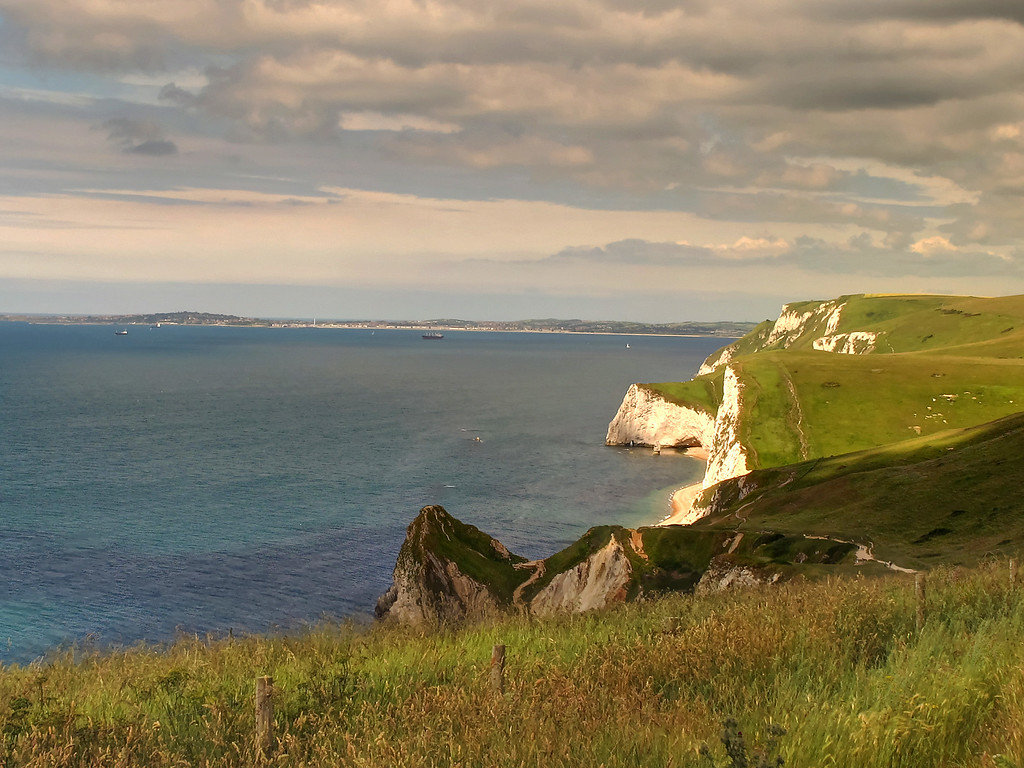 The 'roller coaster' walk ahead from Hanbury Tout, with iconic Durdle Door behind the conical cliff in the centre foreground.