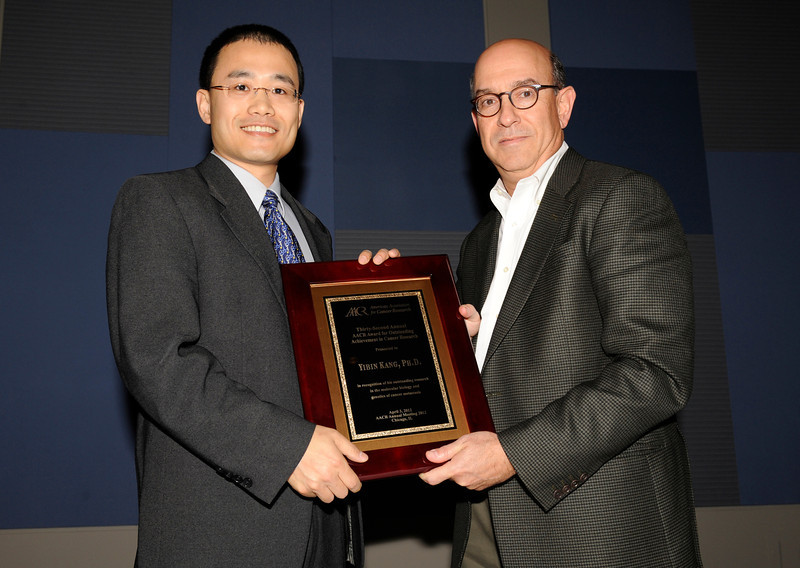 Chicago, IL - The AACR Annual Meeting 2012: Yibin Kang, Ph.D., accepts the 32nd Annual AACR Award for Outstanding Achievement in Cancer Research from Dr. Myles Brown during the American Association for Cancer Research Annual Meeting here today, Tuesday, April 3, 2012. More than 18,000 physicians, researchers, health care professionals, cancer survivors and patient advocates are expected to attend the meeting at McCormick Place. The Annual Meeting highlights the latest findings in all major areas of cancer research from basic through clinical and epidemiological studies. Date: Tuesday, April 3, 2012 Photo by © AACR/Phil McCarten 2012 Technical Questions: todd@toddbuchanan.com; Phone: 612-226-5154.