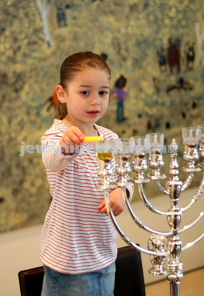 Livia  Slonim lights the first chanukah candle. Photo: peter haskin