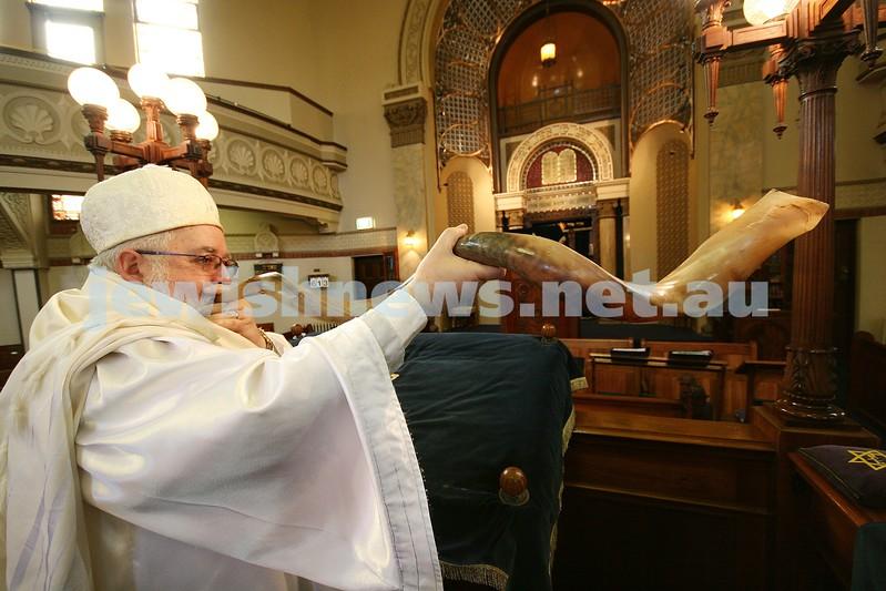 Rabbi Phillip Heilbrunn from St Kilda Shul. Dressed in kittel for Rosh Hashanah blows very large shofar. photo: peter haskin.