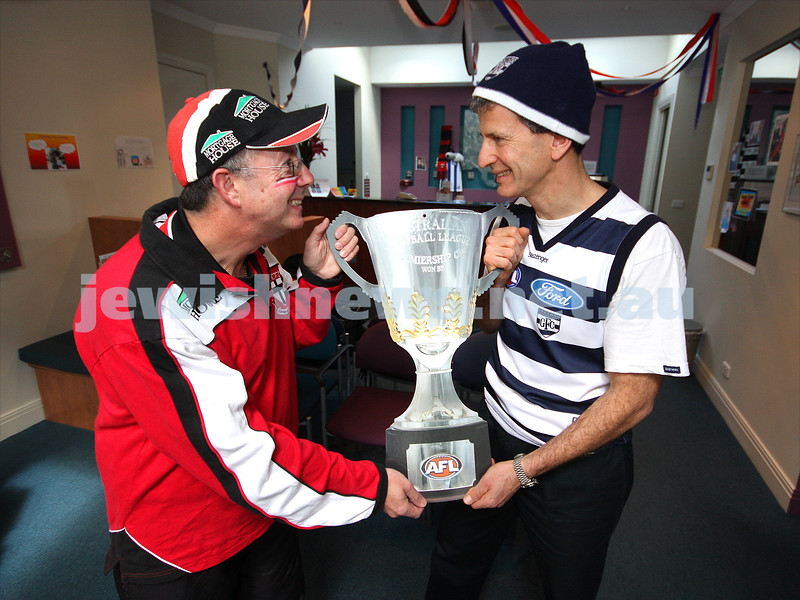 22/9/09. Grand Final 2009. Avid St Kilda supporter Gary Brand (left) with Geelong devotee Jeff Lipshatz. Premiership cup. photo: peter haskin