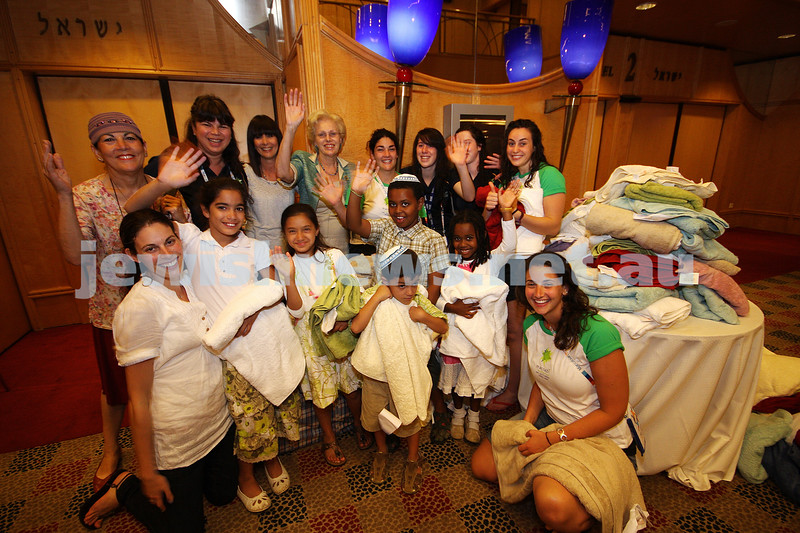 Sandy Sher (back, 2nd from left) with members of Australia's 18th Maccabiah team and some of the Israeli children handing over the towels brought over from Australia. photo: peter haskin