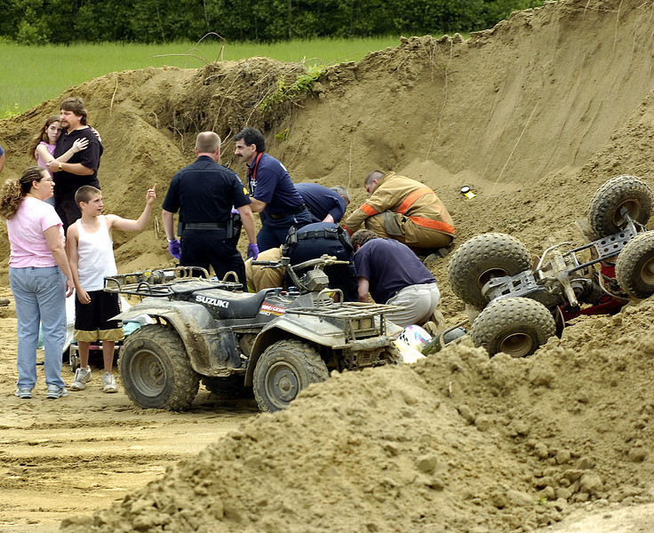 Josh Pomerleau, left explains to his mother Lisa what happened in the sand pit where he was riding on the back of one of the ATV's at right.  His sister Miranda, top left being comforted by their father Eugene was one of the drivers.  Police, fire and United Ambulance personel tend to the other two young boys involved in the accident who were taken to Central Maine Medical Center.