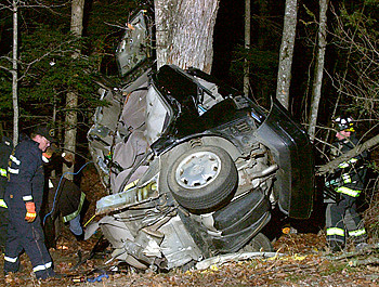 Fire and Recovery personnel from Casco and surrounding towns comb the woods for personal effects before this car was towed from the side of Route 11 in Casco Maine in the early morning hours after five occupants were killed instantly.  Speed and alcohol were contributing factors in the accident.