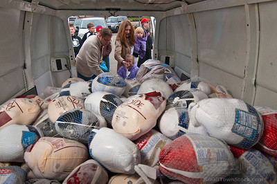 A family adds their selection of frozen turkeys to the stack of almost 300 birds collected Sunday at. St. PaulÕs Catholic church in Westerville. The annual  November collection donations are destined for Holy Rosary-St. John parish in downtown Columbus for its food kitchen.