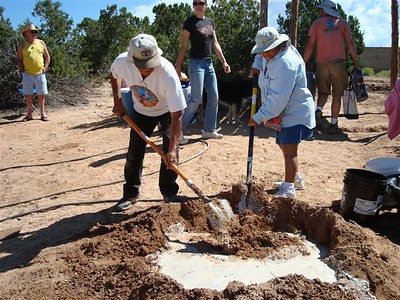 Pueblo elders Larry Littlebird and Cecilia Lucero mixing mud the traditional way